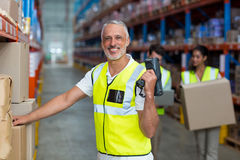 Portrait of smiling warehouse worker scanning box. In warehouse Stock Photography