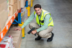 Portrait of smiling warehouse worker scanning box. In warehouse Royalty Free Stock Photo