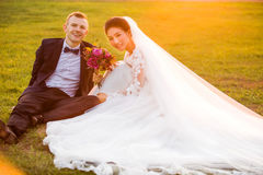 Portrait of smiling wedding couple sitting on grassy field Royalty Free Stock Images
