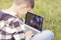 Cheerful teenager chatting on modern laptop stock photography