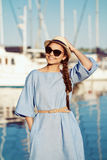 Portrait of smiling white Caucasian brunette woman with tanned skin in blue dress hat, by seashore lakeshore Royalty Free Stock Image