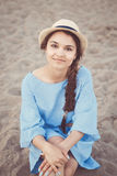 Portrait of smiling white Caucasian brunette woman with tanned skin in blue dress and straw hat sitting on sand beach shore Royalty Free Stock Photos