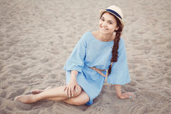 Portrait of smiling white Caucasian brunette woman with tanned skin in blue dress and straw hat sitting on sand beach shore Stock Photo