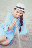Portrait of smiling white Caucasian brunette woman with tanned skin in blue dress and straw hat sitting on sand beach Royalty Free Stock Photography