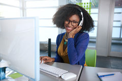 Portrait of a smiling woman with an afro at the. Friendly african american casual business woman working at a desktop computer in a modern withe office Stock Images