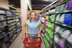 Portrait of a smiling woman is aisle with her trolley Stock Image