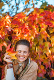 Portrait of smiling woman with autumn leafs in front of foliage Stock Images