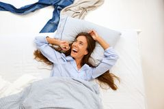 Portrait of a smiling woman awake in bed Stock Photo