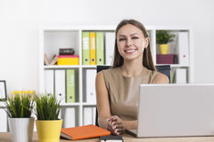 Portrait of a smiling woman in beige in office Royalty Free Stock Images
