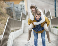 Portrait of smiling woman being piggybacked by man on stairway Stock Photo