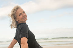 Portrait of smiling woman bending against cloudy sky. At beach Royalty Free Stock Photography