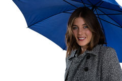 Portrait of smiling woman with blue umbrella. Against white background Stock Image