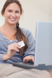Portrait of a smiling woman booking her holidays online Stock Images