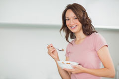 Portrait of smiling woman with a bowl of cereals at home Royalty Free Stock Photo