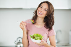 Portrait of smiling woman with a bowl of salad in kitchen Royalty Free Stock Photos