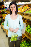 Portrait of a smiling woman buying apple Royalty Free Stock Images