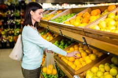 Portrait of a smiling woman buying oranges stock photo