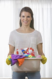 Portrait of smiling woman carrying basket of cleaning supplies at home Stock Photos