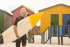 Portrait of smiling woman carrying surfboard while standing against huts stock image