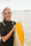 Portrait of smiling woman carrying surfboard while standing on shore. At beach royalty free stock photos