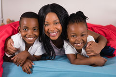 Portrait of smiling woman with children lying on bed Royalty Free Stock Image