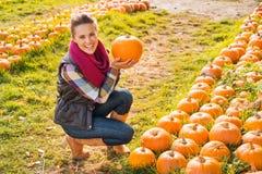 Portrait of smiling woman choosing pumpkin on farm Royalty Free Stock Photos