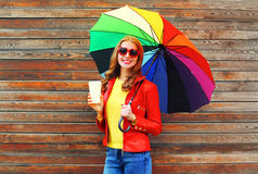 Portrait smiling woman with coffee cup and colorful umbrella in autumn day over wooden background wearing red leather jacket Royalty Free Stock Photography