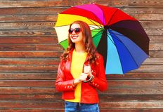 Portrait smiling woman with colorful umbrella in autumn. Over wooden background Royalty Free Stock Image