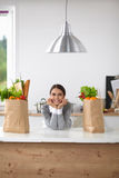 Portrait of a smiling woman cooking in her kitchen Stock Photography