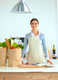 Portrait of a smiling woman cooking in her kitchen Royalty Free Stock Photography