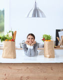 Portrait of a smiling woman cooking in her kitchen Stock Images
