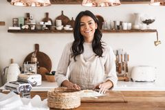Portrait of smiling woman cooking pastry with flour and eggs in kitchen at home. Portrait of smiling brunette woman 30s wearing apron cooking pastry with flour royalty free stock image