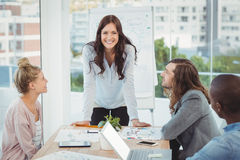 Portrait of smiling woman while coworkers looking at her Stock Photography