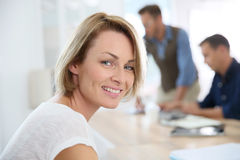 Portrait of smiling woman with coworkers at office Stock Image