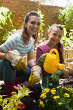 Portrait of smiling woman and daughter crouching by flowers with watering can Stock Photos