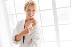 Portrait of smiling woman that dispersing body spray Royalty Free Stock Photography
