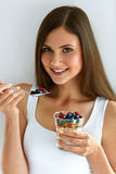 Portrait Of Smiling Woman Eating Yoghurt With Oats And Berries. Woman Eating Healthy Diet Food. Portrait Of Beautiful Happy Young Female Holding Glass Of Natural Stock Images