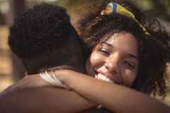 Portrait of smiling woman embracing man while standing on field Royalty Free Stock Photos