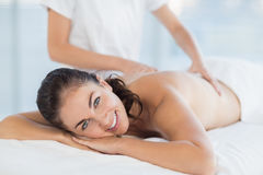 Portrait of smiling woman enjoying massage. Portrait of smiling women enjoying back massage from masseuse at spa Stock Image