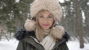 Portrait of smiling woman enjoying wintertime. Woman wearing warm clothes in a cold winter snow forest. Trees on background. Shot on Red Epic Royalty Free Stock Photo