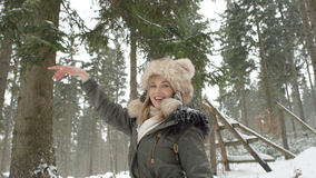 Portrait of smiling woman enjoying wintertime. Woman wearing warm clothes in a cold winter snow forest. Trees on background. Shot on Red Epic Royalty Free Stock Photography