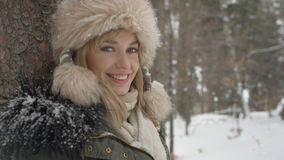 Portrait of smiling woman enjoying wintertime. Woman wearing warm clothes in a cold winter snow forest. Trees on background. Shot on Red Epic Royalty Free Stock Image