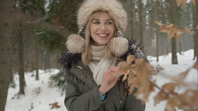Portrait of smiling woman enjoying wintertime. Woman wearing warm clothes in a cold winter snow forest. Trees on background. Shot on Red Epic Stock Image