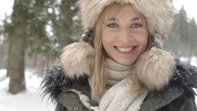 Portrait of smiling woman enjoying wintertime. Woman wearing warm clothes in a cold winter snow forest. Trees on background. Shot on Red Epic Stock Photos