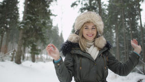 Portrait of smiling woman enjoying wintertime. Woman wearing warm clothes in a cold winter snow forest. Trees on background. Shot on Red Epic Royalty Free Stock Images