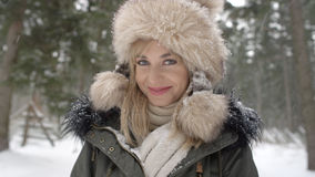 Portrait of smiling woman enjoying wintertime. Woman wearing warm clothes in a cold winter snow forest. Trees on background. Shot on Red Epic Royalty Free Stock Photos