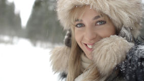 Portrait of smiling woman enjoying wintertime. Woman wearing warm clothes in a cold winter snow forest. Trees on background. Shot on Red Epic Stock Images