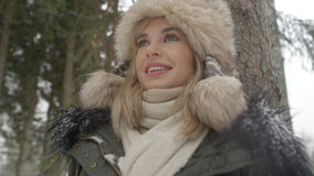 Portrait of smiling woman enjoying wintertime. Woman wearing warm clothes in a cold winter snow forest. Trees on background. Shot on Red Epic Stock Photography