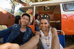 Portrait of smiling woman with friends taking selfie at campsite Royalty Free Stock Photos