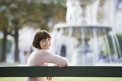 Portrait Of Smiling Woman In Front Of Blurred Fountain Stock Image